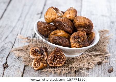 Figs (dried) on a wooden background - stock photo