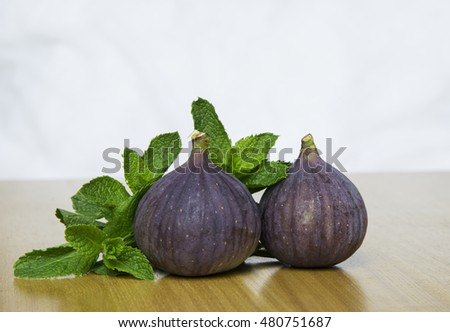 figs fruit with fresh mint on wooden with white background