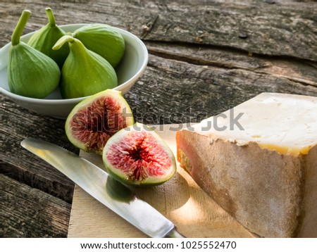 Figs in a bowl and cheese on a wooden cutting board with knife