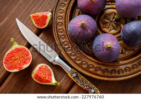 figs in a bowl and on rustic wooden table - stock photo