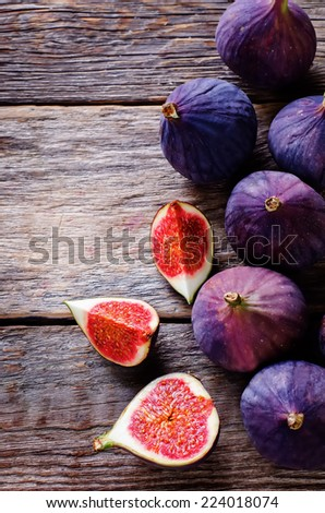 figs on a dark wood background. tinting. selective focus on the figs slices - stock photo