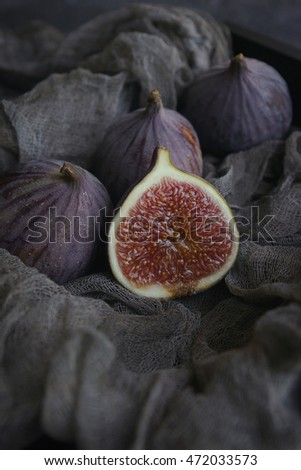 Figs on dark fabric in a wooden box on a dark stone background, Close-up, Selective focus