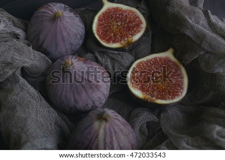 Figs on dark fabric in a wooden box on a dark stone background, Selective focus
