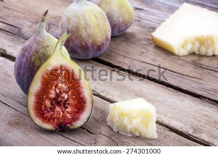 Figs whole and halved with cheese shot on wood at an angle front on landscape - stock photo