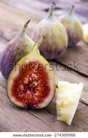 Figs whole and halved with cheese shot on wood at an angle front on portrait - stock photo