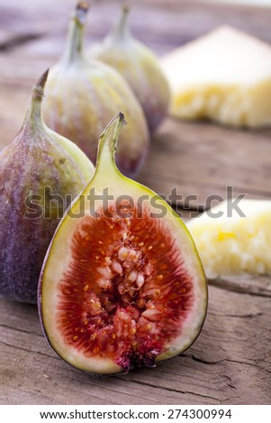 Figs whole and halved with cheese shot on wood front on portrait - stock photo