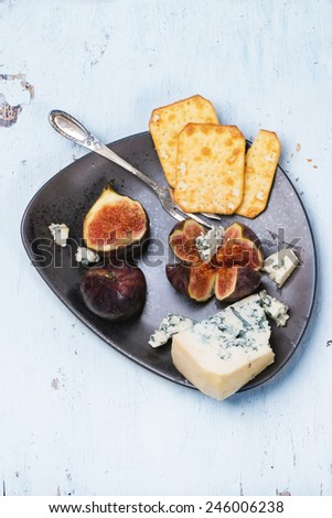 Figs with blue cheese and crackers on ceramic plate. Top view. See series.