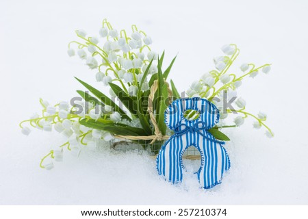 Figure 8 and lilies of the valley in basket on snow, close-up - stock photo