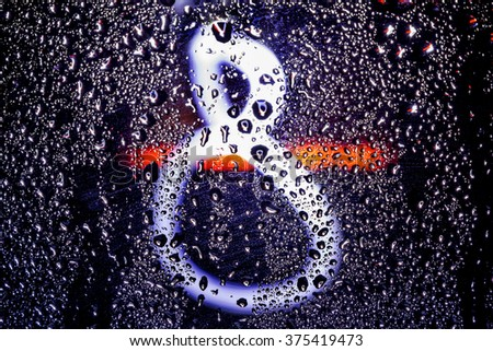 Figure eight glows through the wet glass amid colorful Bokeh