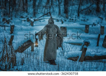 Figure of a man from the back with a scythe of death. He brings the horror and fear of death. - stock photo