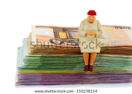 figure of an old woman sitting on a stack of bills, symbolic photo for pension and retirement - stock photo