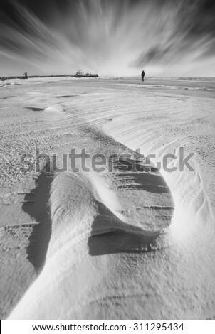 Figure of lonely man on a frozen Black sea. Winter landscape. Monochrome colors - stock photo