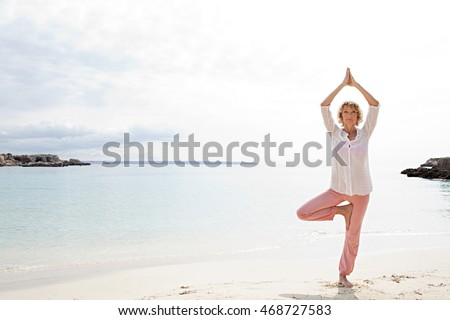 Figure of mature beautiful woman in tree yoga position, on shore of inviting, calm blue sea destination white sand beach, sunny holiday, outdoors. Healthy travel fitness lifestyle.