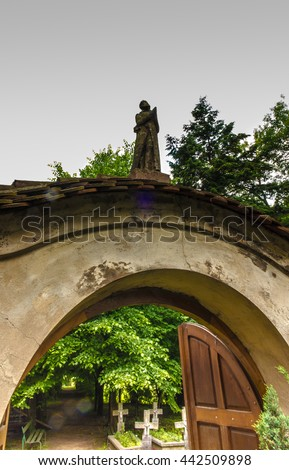 Figure of praying monk on the gate leading to the cemetery, the nuns of the Benedictine abbey, Staniatki near Krakow in Poland - stock photo