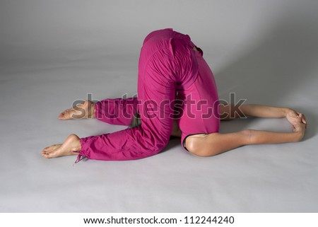 Figure of the young woman in sportswear on a dark background - stock photo