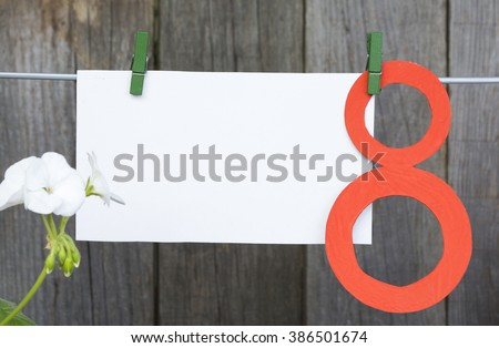 figure 8, paper envelope hang on clothespins in front of wooden background. International Women's Day. March 8, Happy Women's Day greeting message text