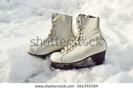 Figure skates in snow close-up - stock photo