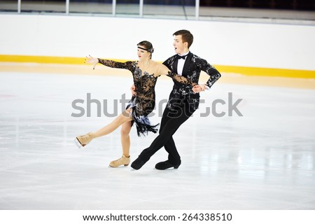 figure skating of young skaters pair at sports arena - stock photo