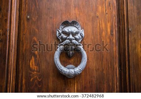 Figured door knocker on old wooden door - stock photo