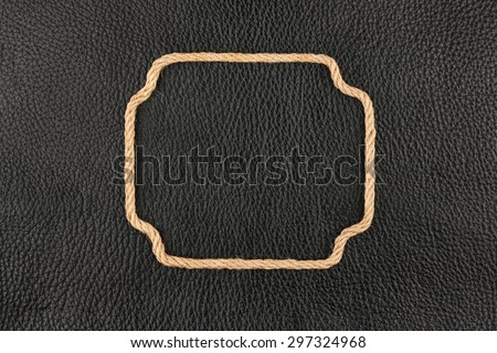 Figured frame made of rope lying on the natural leather, with space for advertising - stock photo
