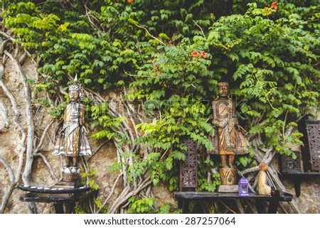 figures and wood carvings surrounded by ivy and vegetation