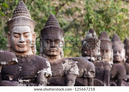 Figures guardians statues of Angkor Thom south door, Cambodia - stock photo