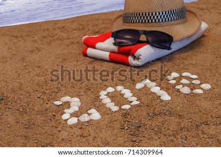 figures of coming New year on the sand and beach accessories closeup/Christmas background with hat, towel and goggles