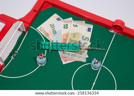 Figures of football players on euro banknotes,  syringe - stock photo