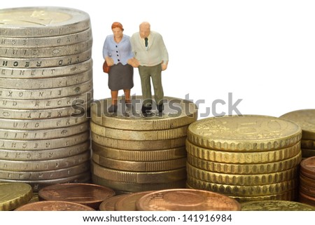 Figurine from senior couple with euro coins on white background - stock photo