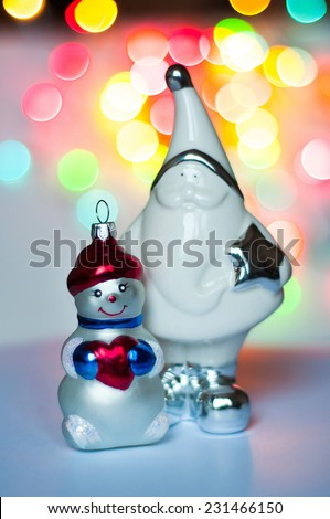 Figurine of Santa Claus and Snowman in the background of multi-colored lights - stock photo