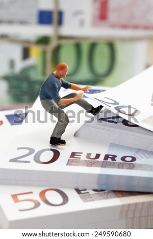 Figurine of worker climbing on stack of euro note - stock photo
