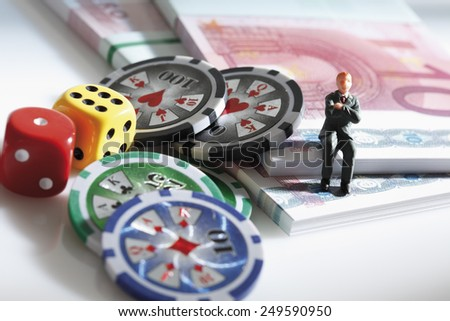 Figurine sitting on euro notes with dices and jetons - stock photo