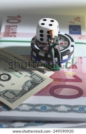 Figurine sitting on jetons with dice and banknotes - stock photo
