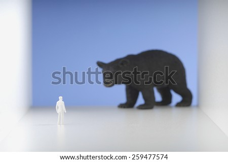 Figurine standing in front of bear. - stock photo
