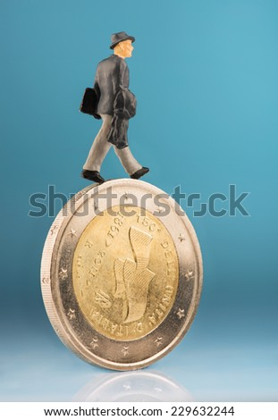 Figurine walking on one euro coin - stock photo