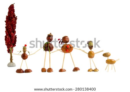 Figurines made of chestnuts and acorns and matches representing family with dog by tree isolated on white - stock photo