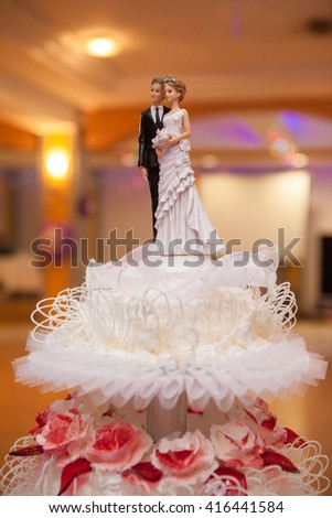 figurines of the bride and groom on wedding cake - stock photo