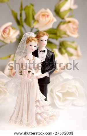 Figurines of wedding couple on light background with roses.