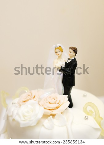 Figurines on top of wedding cake  - stock photo