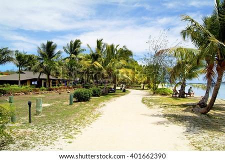 Fiji, bungalows and cocos palms on Malolo Lailai island - stock photo