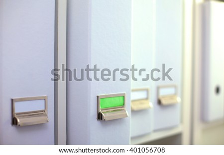 File folders, standing on  shelves in the background - stock photo