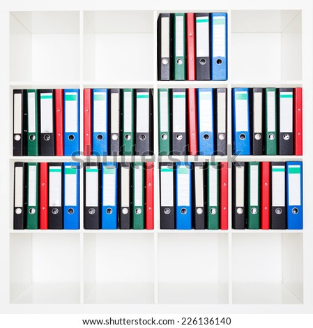 File folders, standing on the shelves at office. - stock photo