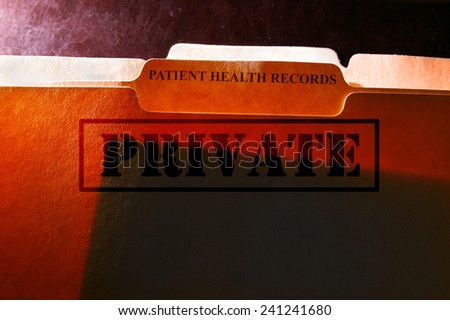 File folders with Patient Health Records label and Private stamp - stock photo
