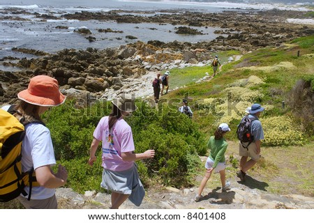 File of hikers walks down to sea beach next to awesome mountains. Shot near Strand, Pringle and Betties Bays, Western Cape, South Africa. - stock photo