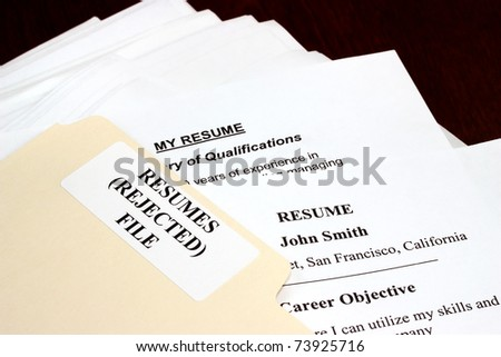 File with stack of rejected resumes