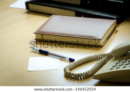 Files, notebooks, phones, pens and paper on the desk at the office. - stock photo
