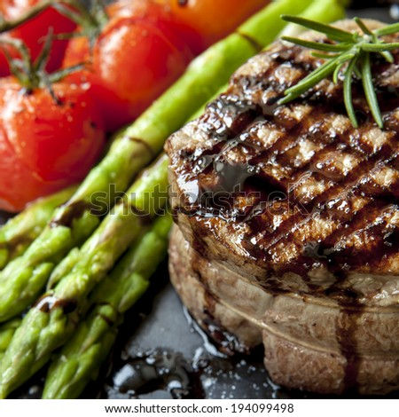 Filet mignon grilled beef steak, with asparagus and cherry tomatoes.  Isolated on white. - stock photo