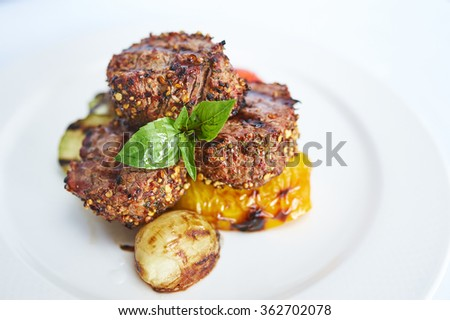 Filet mignon with grilled vegetables on white plate studio shot - stock photo