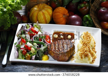 Filet mignon with vegetables and mashed potato salad. - stock photo