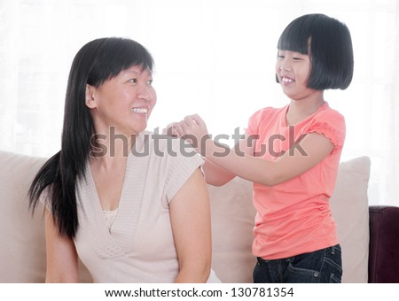Filial piety concept. Southeast Asian child doing shoulder massage to her mother at home. - stock photo